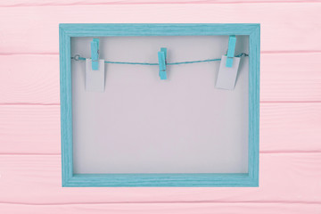 Empty wooden frame. Close-up of empty blue wooden frame with a clothesline and clothespins on background of frame Isolated on a pink board . Food recipe, valentine, mothers day or other festivals.