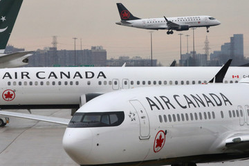 Two Air Canada Boeing 737 MAX 8 aircrafts are seen on the ground as Air Canada Embraer aircraft flies in the background at Toronto Pearson International Airport
