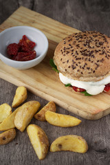 Homemade hamburger with wholemeal bread, on wooden background. Rustic burger and rustic potato.