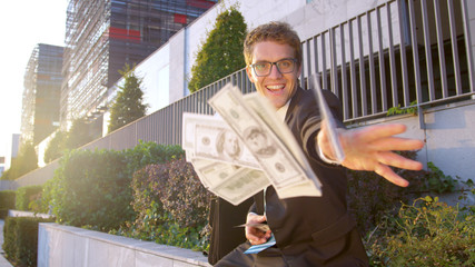 SUN FLARE, PORTRAIT: Happy businessman throws a bunch of money at the camera.