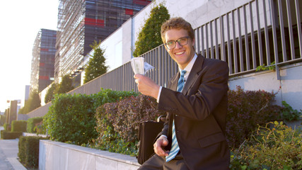 PORTRAIT: Cheerful young Caucasian businessman smiles and waves his money.