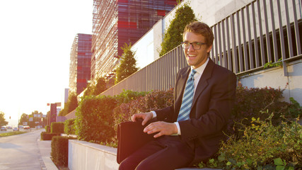 LENS FLARE: Cheerful businessman sitting on a ledge and singing after promotion