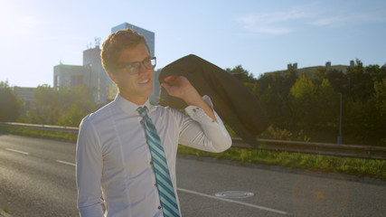 CLOSE UP: Yuppie flips his jacket over his shoulder while walking to office.