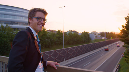 PORTRAIT: Successful yuppie turns around while watching sunset above the highway