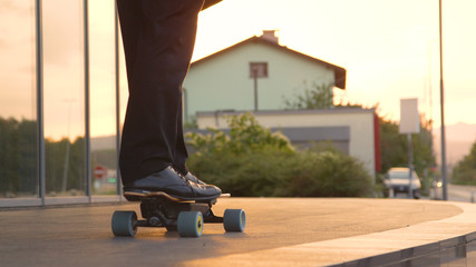 CLOSE UP: Unrecognizable yuppie going home from work on his electric skateboard