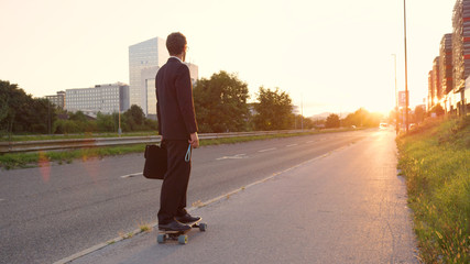 LENS FLARE: Active businessman cruising down the sunlit street on his longboard.