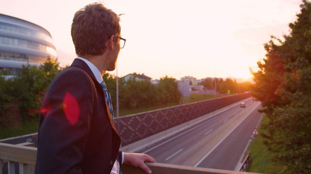 CLOSE UP: Young businessman lost in thought watches the busy highway below him.