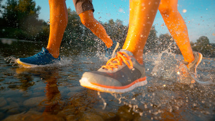 LOW ANGLE: Young athletic couple running in shallow river water on sunny day.