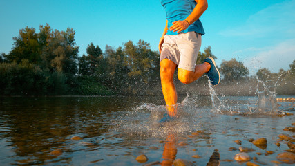 LOW ANGLE: Cool shot of sportsman going for a jog on the riverbank.