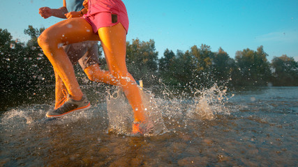 CLOSE UP: Fit couple running through idyllic forest and in the shallow stream.
