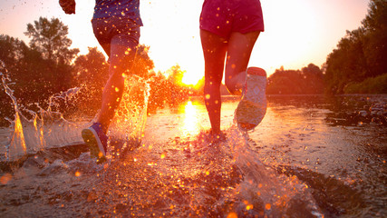 LENS FLARE: Unrecognizable couple jogging in shallow stream and towards sunset.