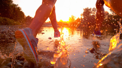 SUN FLARE: Fit training partners run in refreshing river water towards sunset.