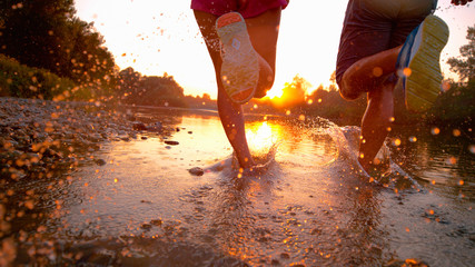 CLOSE UP: Glassy drops of water fly as athletic couple jogs in shallow river.