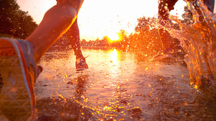 SUN FLARE Unrecognizable man and woman splash the refreshing water while jogging