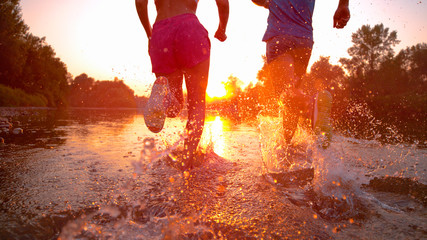 LENS FLARE: Golden sunbeams shine on fit couple jogging in the tranquil stream.