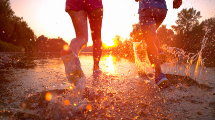CLOSE UP: Athletic couple jogs in the cold stream water at beautiful sunset.
