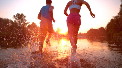 CLOSE UP Unrecognizable woman and man running towards sunset and splashing water