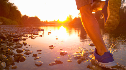 CLOSE UP: Unrecognizable sportsman running in the river shallows at golden hour.