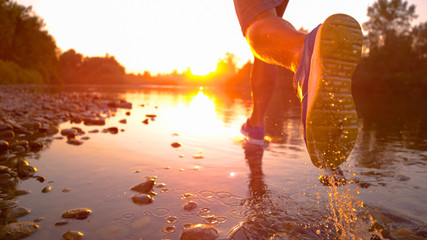 LENS FLARE, CLOSE UP Unrecognizable sportsman jogging in shallow river at sunset