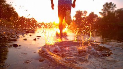 SUN FLARE CLOSE UP: Athletic man runs in the shallow stream towards the sunset.