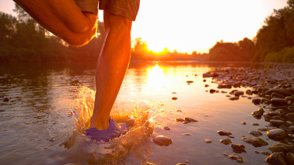 LOW ANGLE: Cinematic shot of young male runner's legs splashing the stream water