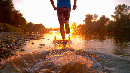 LOW ANGLE, DOF: Unrecognizable male runner splashing the glassy river water.