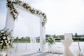Wedding set up, outdoor wedding reception with arch  on the shore of the lake