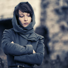 Sad young fashion woman in classic coat and headscarf