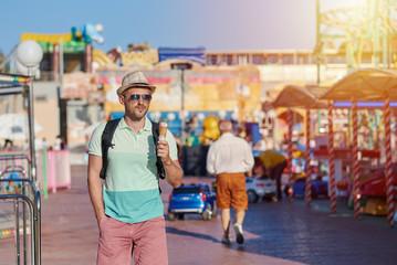 European tourist is eating tasty ice-cream in the amusement park.