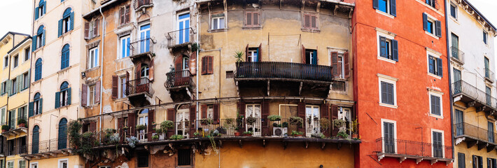 Typical old italian building facade in Verona with balconies and flowers