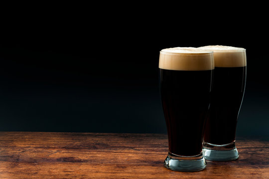 Alcohol abuse, bitter refreshing alcoholic beverage and dry stout concept theme with frothy glass pints of dark beer on wood table isolated on black background with copyspace in bar or pub setting