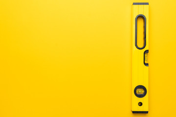 yellow spirit level on the yellow background with some copy space