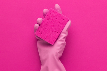 hand in protective glove holding red sponge over purple background