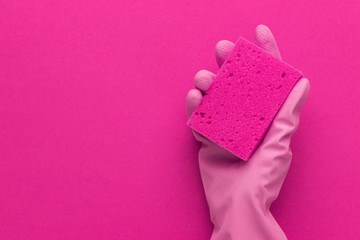 hand in protective glove holding red sponge over purple background with copy space