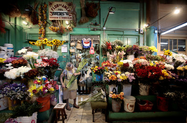 A woman sells flowers in the Central Market in San Jose