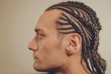 male hairstyle close-up braids, hair braided, pensive look, man portrait