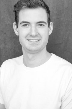 Model posing for the camera for a headshot in front of textured black background wearing a t-shirt, no facial hair. Clean cut guy, white, brown hair. Active lifestyle concept black and white.