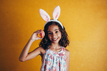 A happy girl showing decorated easter eggs