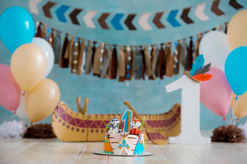 Decorated photo zone for 1 year Indian Apache chief with a canoe for a children's party. First birthday and smash cake