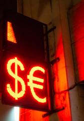 Glowing Dollar - Euro neon sign in the street