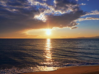 Beautiful and serene sunset on the beach - sunrays shining through the clouds