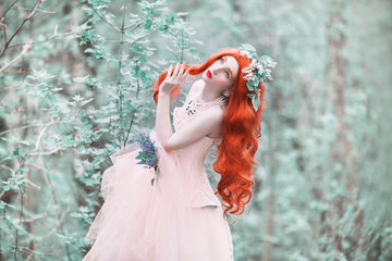 Redhead girl in fantasy world with very long hair in pink dress on spring background. A beautiful girl with flower bouquet in forest. Renaissance fantasy woman in spring forest. Flower wreath.