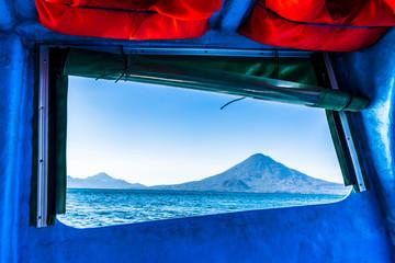 View of Atitlan & Toliman volcanoes through open boat window, Lake Atitlan, Guatemala, Central America