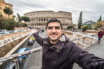 Young pretty man at colosseum taking selfies with smartphone in Rome city centre on sunny