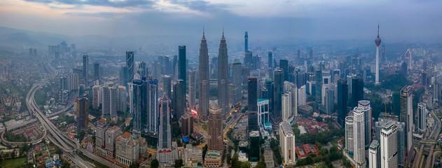 Aluminium Prints Kuala Lumpur KUALA LUMPUR, MALAYSIA - MARCH 9, 2019: Dramatic aerial panorama photograph of Kuala Lumpur city skyline during hazy sunrise.