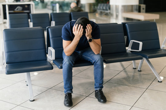 Problem with transportation, delay of flight, depressed commuter with his luggage. Sad man late to flight or wait for flight.