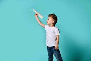Little boy with cool haircut play with a paper plane and looks at it. childhood. imagination.