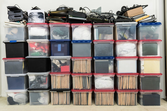 Tall wall of plastic file storage boxes with folders, binders and miscellaneous business office supplies.