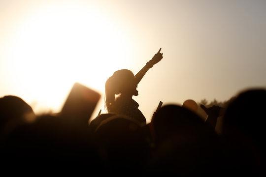 Girl enjoying concert, having fun on a friend's shoulders