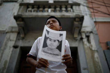 A child holds a picture of a missing person during a protest against a bill that would grant amnesty to war crimes committed during country's 36 year civil war outside the Congress, in Guatemala City
